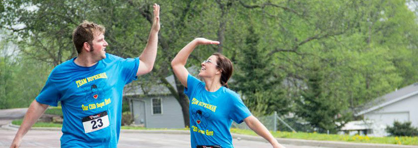 Two runners high five each other during a fun run